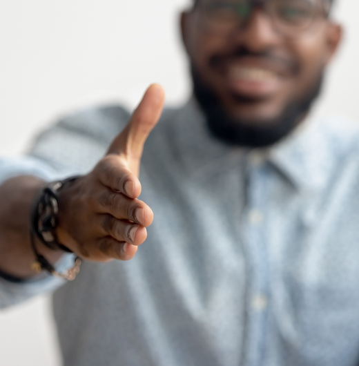a Black man in professional attire extends his hand for a handshake