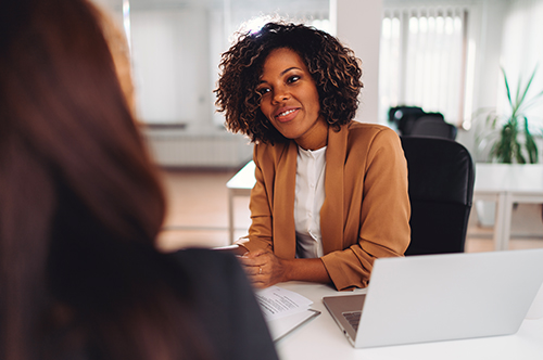 a Black woman in professional attire leans forward toward to speak to another woman