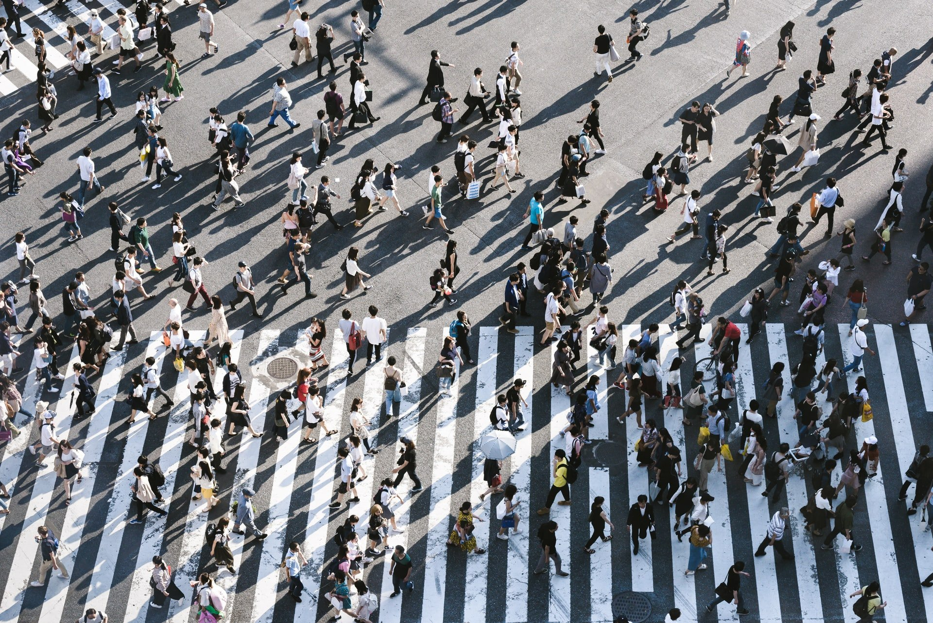 crowd of people crossing road in all directions