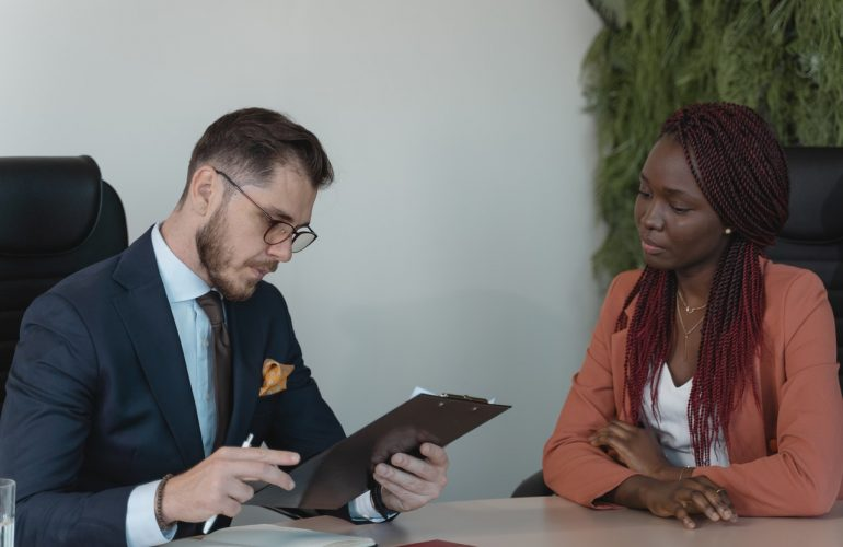 man looking at clipboard talking to woman