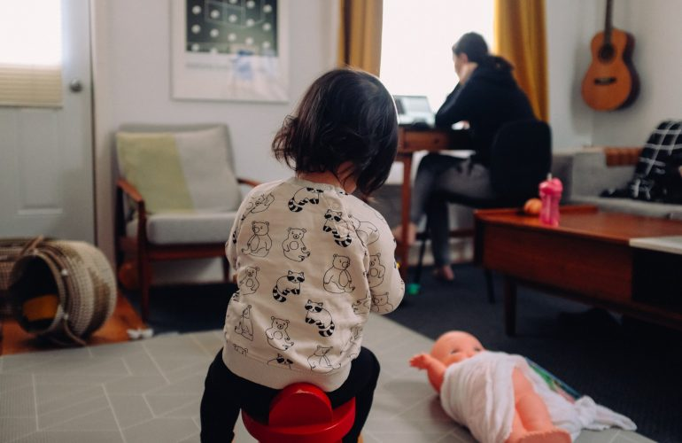 Child playing while parent works on computer in background